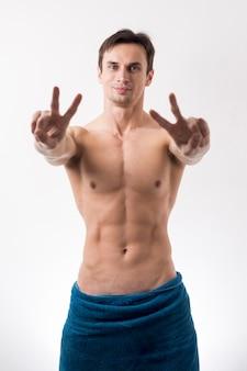 Toplesser mann des mittleren schusses, der friedenszeichen gestikuliert