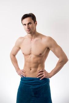 Toplesser mann des mittleren schusses, der im badtuch aufwirft