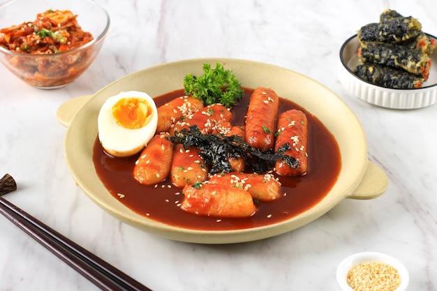 Topokki oder tteokbokki ist gebratener reiskuchen mit gemüse und fischkuchen in scharfer sauce