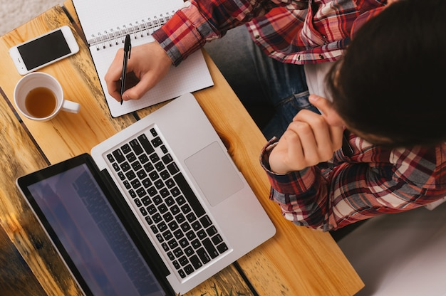 Topview des mannes arbeitend an computer und eine anmerkung zu schreibend