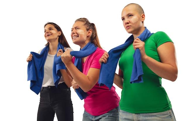 Tor. weibliche fußballfans, die für lieblingssportmannschaft mit hellen emotionen jubeln, die auf weißem studiohintergrund lokalisiert werden.