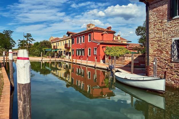 Torcello, venedig. bunte häuser auf torcello-insel, kanal und booten. sommer, italien