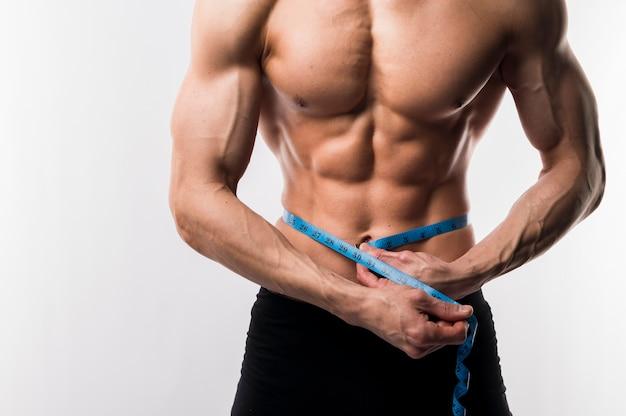 Torso des hemdlosen athletischen mannes mit maßband
