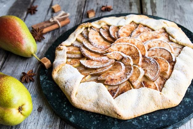 Torte mit äpfeln, birnen und zimt auf einem alten hölzernen hintergrund