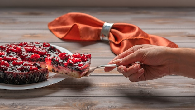 Torte mit beeren himbeeren erdbeeren johannisbeeren auf einem weißen teller womans hand hält ein stück