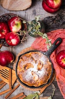Torte mit den äpfeln, die eine eisenwanne ausfüllen. reife äpfel auf einem holztisch, draufsicht