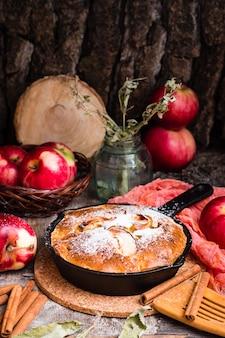 Torte mit den äpfeln, die eine eisenwanne ausfüllen. reife äpfel auf einem holztisch.