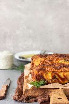 Torte mit der leber, ei und dill, die auf ein hölzernes brett füllen.