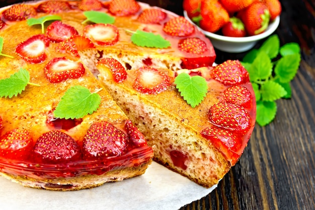 Torte mit erdbeere, kissel, gelee und minze auf pergamenthintergrund auf holzbrett