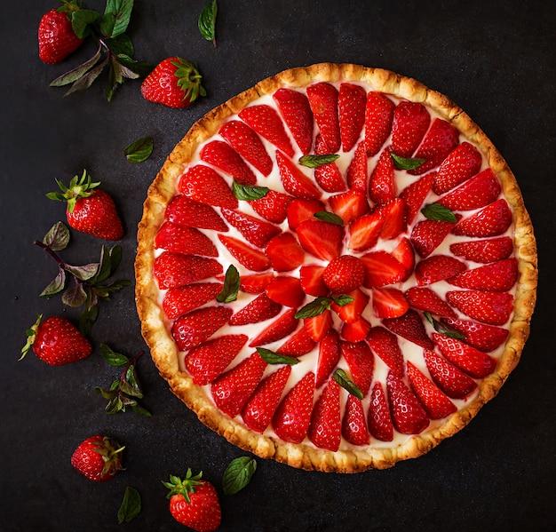 Torte mit erdbeeren und schlagsahne, dekoriert mit minzblättern. draufsicht