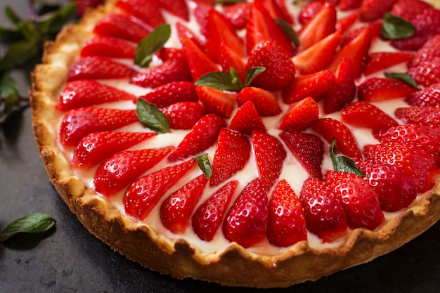 Torte mit erdbeeren und schlagsahne, dekoriert mit minzblättern.