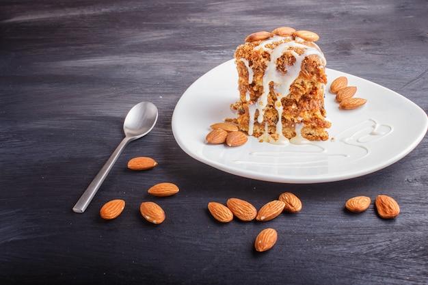 Torte mit karamell, weißer milchsoße und mandeln auf einer weißen platte auf einem schwarzen hölzernen hintergrund