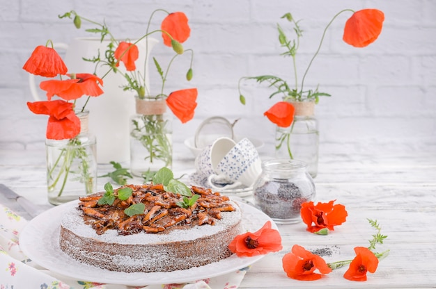 Torte mit mohn auf einem weißen hintergrund. hausgemachtes gebäck und rote blumen