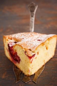 Torte mit pflaumen in puderzucker.