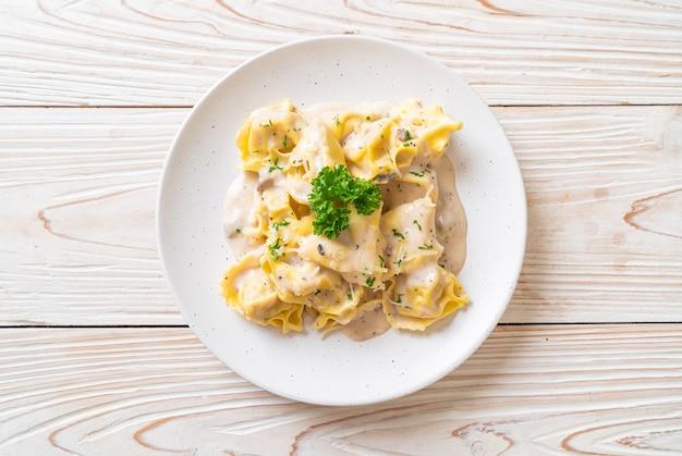 Tortellini-nudeln mit champignon-sahne-sauce und käse - italienische küche