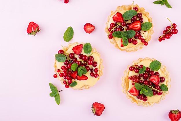 Torten mit erdbeeren, johannisbeeren und schlagsahne, dekoriert mit minzblättern