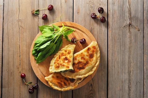 Torten mit spinat und kirsche auf holz