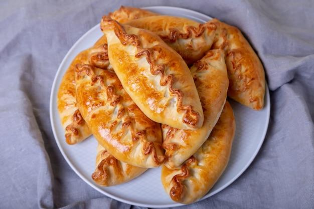 Torten (pirozhki) mit kohl. hausgemachtes backen. traditionelle russische und ukrainische küche. im hintergrund ist ein gericht mit kuchen. nahansicht.