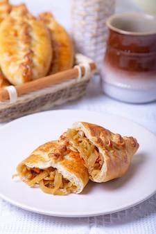 Torten (pirozhki) mit kohl. hausgemachtes backen. traditionelle russische und ukrainische küche. im hintergrund ist ein korb mit kuchen. nahansicht.