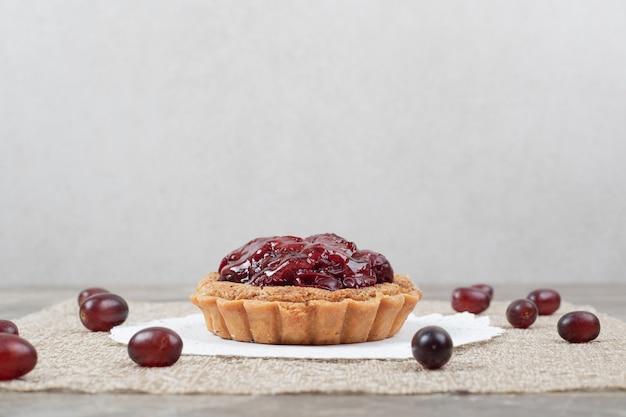 Tortenkuchen mit früchten auf sackleinen und trauben. hochwertiges foto