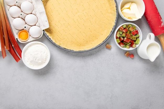 Tortenkuchenzubereitung, rezeptteig mit ei, sahne, mehl, butter, rhabarber und nudelholz auf grauem hintergrund. kopierraum, draufsicht