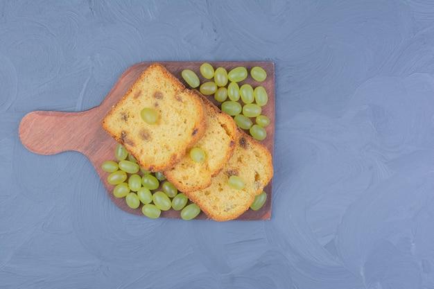 Tortenscheiben mit grünen trauben auf einer holzplatte.