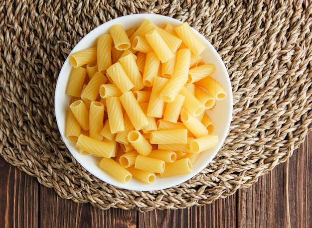 Tortiglioni-nudeln in einer schüssel auf tischset aus holz und weide, flach gelegt.