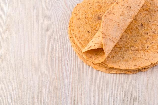 Tortilla auf hölzernem tischhintergrund