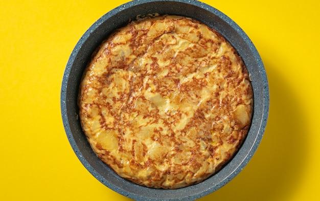 Tortilla de patatas auf bratpfanne auf gelbem, typisch spanischem teller.