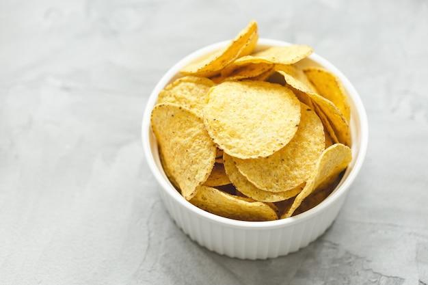 Tortilla-mais-chips in der schüssel auf grauem hintergrund