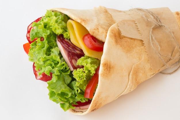 Tortilla mit kräutern, käse und fleisch rollen