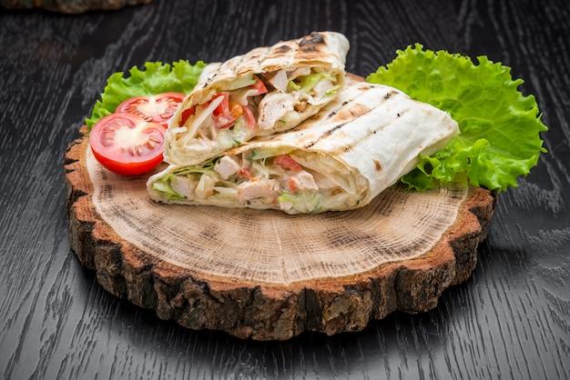 Tortilla wickelt mit gegrilltem huhn oder vegetarischem tarteel frischem gemüse auf einem hölzernen hintergrund ein