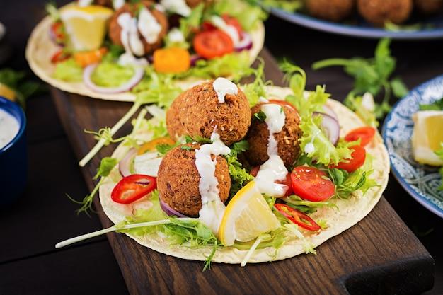 Tortilla wrap mit falafel und frischem salat. vegane tacos. vegetarisches gesundes essen.