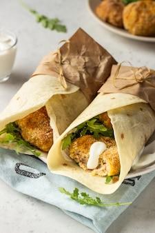 Tortilla wraps mit hähnchen- oder putenschnitzel, rucola und sauerrahmsauce.