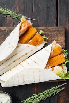 Tortillarolle mit fischstäbchen, käse und gemüse, auf holzschneidebrett, auf altem dunklem holztisch, draufsicht flach gelegt