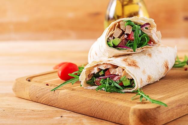 Tortillas wickeln mit huhn und gemüse auf hölzernem hintergrund ein. hähnchen-burrito. gesundes essen.