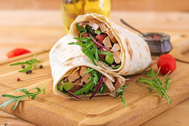 Tortillas wickeln mit huhn und gemüse auf hölzernem hintergrund ein.