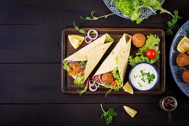 Tortillaverpackung mit falafel und frischem salat. vegane tacos. vegetarisch gesundes essen. ansicht von oben