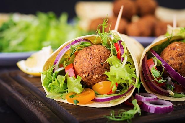 Tortillaverpackung mit falafel und frischem salat. vegane tacos. vegetarisch gesundes essen.