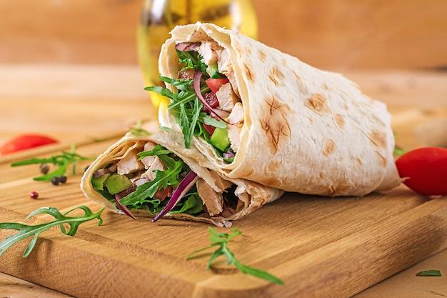 Tortillaverpackungen mit huhn und gemüse auf holztisch. hähnchen-burrito. gesundes essen.