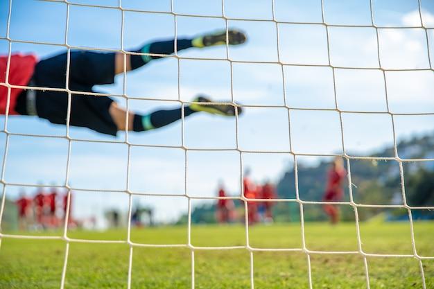 Torwart, der einen ball während eines fußballspiels fängt