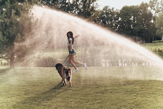 Total glücklich. in voller länge der schönen jungen frau, die mit ihrem hund spielt, während sie draußen unter wasser läuft