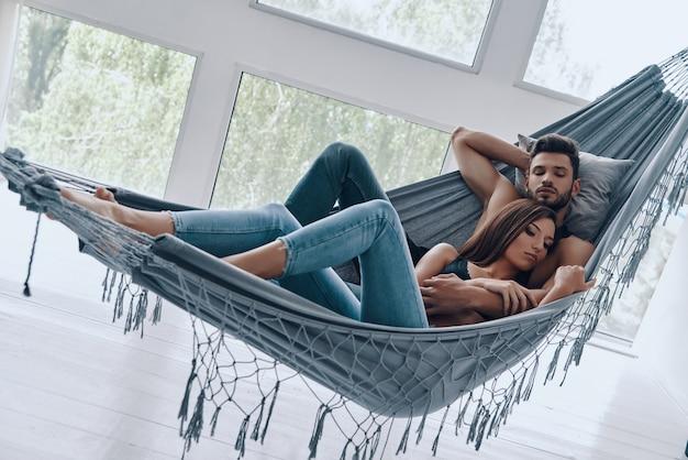Total verliebt. schönes junges paar umarmt beim schlafen in der hängematte drinnen