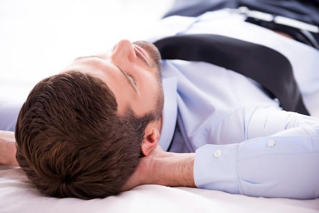 Totale entspannung. rückansicht eines jungen mannes in hemd und krawatte, der die hände hinter dem kopf hält, während er im bett schläft
