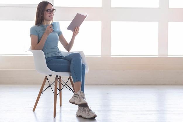 Totale frau, die auf stuhl beim ablesen eines buches sitzt
