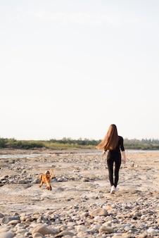 Totale frau mit ihrem hund spazieren
