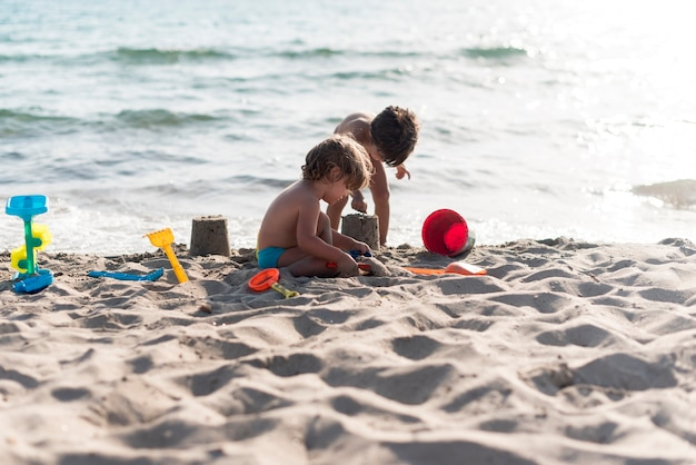 Totale geschwister machen sandburgen am strand