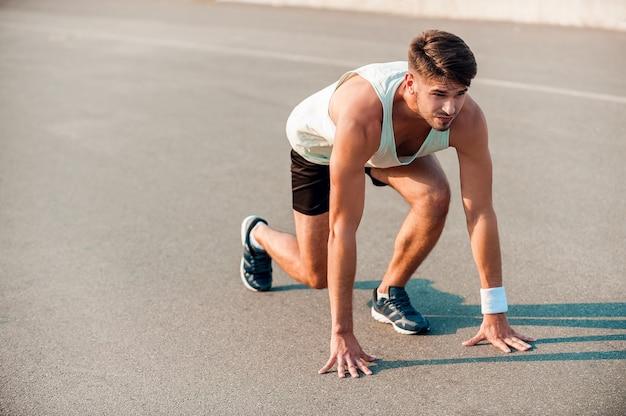 Totale konzentration. selbstbewusster junger muskulöser mann, der in der startlinie steht und nach vorne schaut