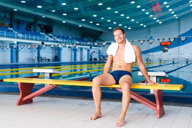 Totale schwimmerin posiert mit handtuch auf den schultern