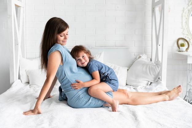Totale tochter, die auf ihrer schwangeren mutter bleibt